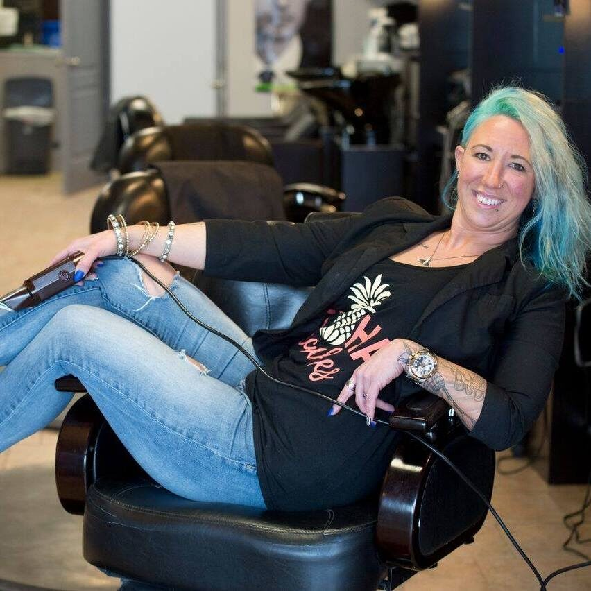 Barber Lounge Owner Jehane Miller sits in a barber chair.